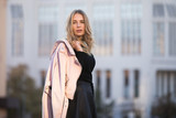Autumn fashion. Stylish woman keeps her jacket over shoulder standing against european building background. - 174722815
