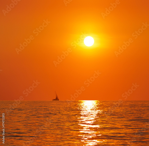 Foto op Canvas Baksteen Sunset or sunrise over the sea. On the horizon a yacht.