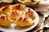 Baked dumplings stuffed with cheese and potatoes sprinkled with pork greaves  on a white plate - 174736493
