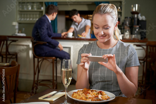 Food Blogger Taking Picture Of Restaurant Meal On Mobile Phone