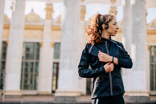 Fototapeta Young female athlete listening portable music player outdoors