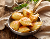 Baked dumplings stuffed with curd cheese and potatoes in a pan on a wooden table - 174754663