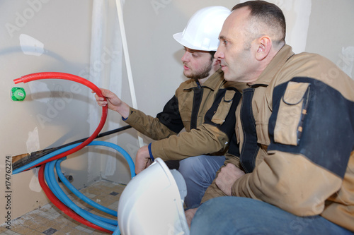 construction electricians feeding wires Poster