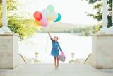 Cheerful girl holding colorful balloons and childish suitcase  - 174765031