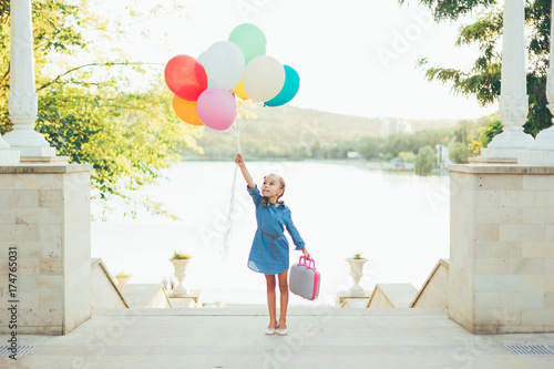Fototapeta Cheerful girl holding colorful balloons and childish suitcase