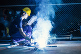 Worker while doing a welding with arc welder with the smoke, man wearing mask with his hands welding in heavy industry - 174777027