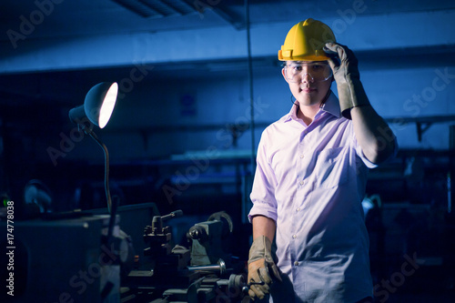 Portrait of young adult experienced industrial asian worker over industry machin Poster