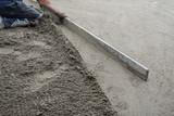 Construction worker kneeling, flattening the cement floor with a hand leveler  - 174782008