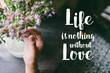Life quote. Motivation quote on soft background. The hand touching purple flowers. Life is nothing without love.