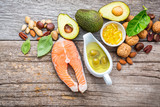 Selection food sources of omega 3 and unsaturated fats. Superfood high vitamin e and dietary fiber for healthy food. Almond,pecan,hazelnuts,walnuts,olive oil,fish oil and salmon on wooden background. - 174808825