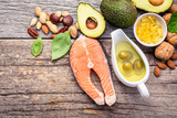 Selection food sources of omega 3 and unsaturated fats. Superfood high vitamin e and dietary fiber for healthy food. Almond,pecan,hazelnuts,walnuts,olive oil,fish oil and salmon on wooden background. - 174808851