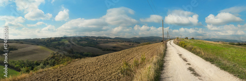 Staande foto Beige Panoramic view of a rural landscape with plowed fields and white country road