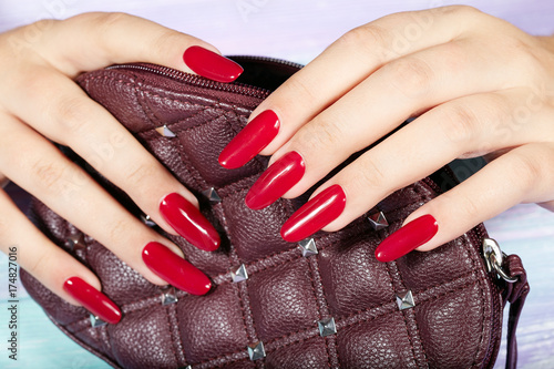 Fotobehang Manicure Hands with long artificial manicured nails colored with red nail polish holding a handbag