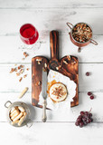 A glass of red wine, baked camembert cheese with honey and walnuts on a wooden vintage cutting board, fresh grapes, knife, grissini breadsticks on a white wooden background. View from above - 174829430