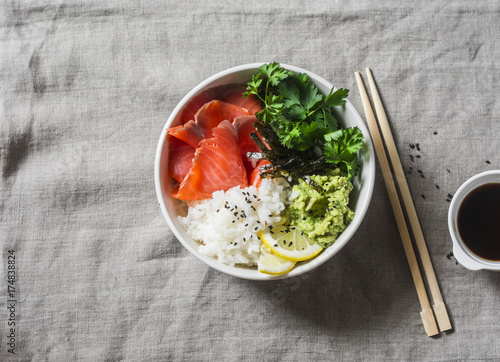 Papiers peints Sushi bar Smoked salmon sushi bowl on grey background, top view. Rice, avocado puree, salmon - healthy food concept. Asian style food