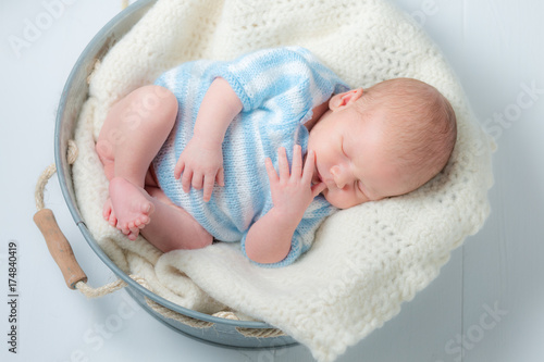 Cute newborn infant sleeping in small bath Poster
