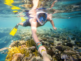 man snorkel in shallow water on coral fish - 174846263