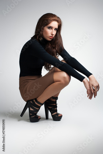 Keuken foto achterwand Kapsalon young beautiful brunette fashion woman. sitting on floor on grey background