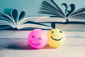 Self made hand drawn smiley face ball in yellow and pink surrounded by a lot of books - Retro Vintage filte