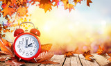 Daylight Savings Time Concept - Clock And Leaves On Wooden Table  - 174853003