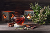 still life with a cup of tea, spices, candles and heather on a dark wooden background - 174856068