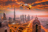 Airplane is flying over Dubai against colorful sunset in United Arab Emirates - 174864041