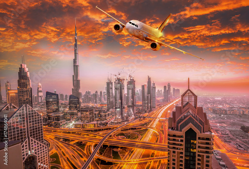 Airplane is flying over Dubai against colorful sunset in United Arab Emirates Poster