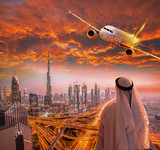 Arabian man with airplane flying over Dubai against colorful sunset in United Arab Emirates