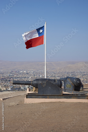 Historical relics from the War of the Pacific along with a Chilean flag on the  Morro de Arica in the coastal city of Arica in northern Chile Poster