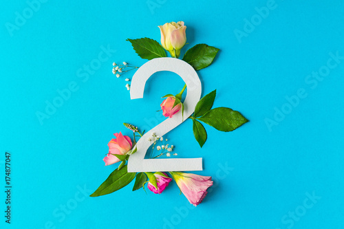 Composition with number 2 and beautiful flowers on color background
