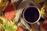 Cup of coffee, a sweater, and autumn leaves lit by sunlight from the window. Toned, top view - 174885052
