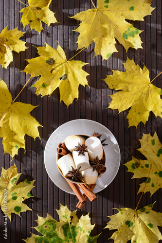 Cup of coffee with marshmallows and yellow maple leaves lit by sunlight from the window. Top view - 174885076