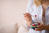 Woman sitting on a sofa and eating organic vanilla yogurt with blueberries and raspberries. Healthy breakfast at home. - 174891265