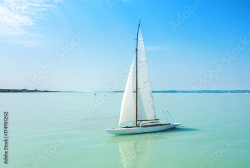 A view from a ship to bright Balaton lake water and a white yacht on sunny summer day, Hungary Poster