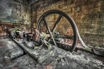 Antique belt driven steam engine in an abandoned factory