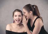 girl telling secret things to her girlfriend - 174907458