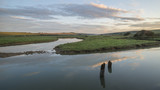 Beautiful dawn landscape over English countryside with river slowly flowing through fields - 174908666