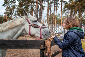 Beautiful young woman is feeding horse with hands