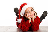 Adorable little girl wearing santa hat laying on wooden floor - 174911261