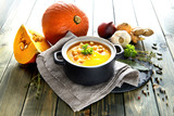 Spicy pumpkin creme soup with carrot and chili pepper on wood - 174914020