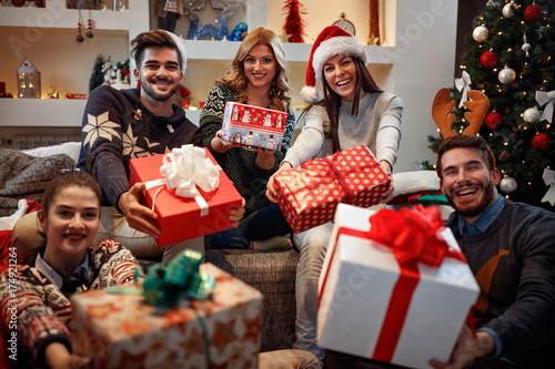 Young happy people with gifts for Christmas