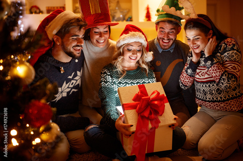 Surprised woman and friends with Christmas gift in opening box