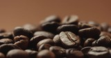 Pan close up video of freshly roasted coffee beans isolated on brown - 174930837