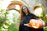 Long-haired girl with carved ripe pumpkin looking at camera - 174935003