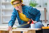 Female repairman carpenter cutting joining wooden planks doing r - 174935406