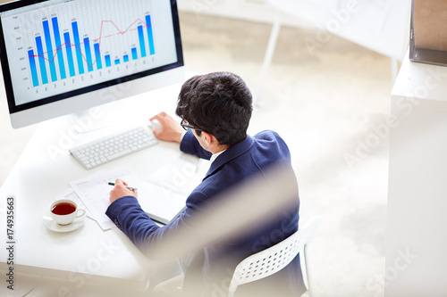 Contemporary financial specialist sitting by workplace in front of computer monitor and analyzing online chart and graph
