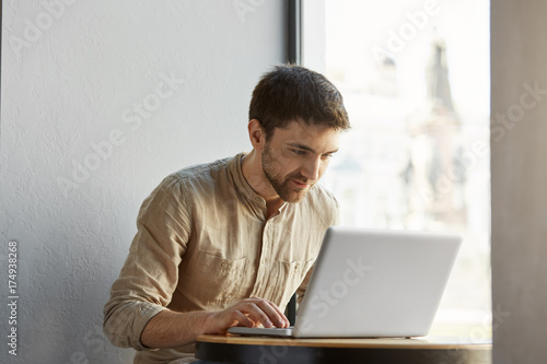 Portrait of attractive caucasian freelance male in casual clothes working hard on his laptop computer in cafe with happy expression. Business concept.