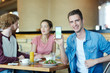 Happy guy with smartphone showing promo advert of new diner where he having lunch with his friends