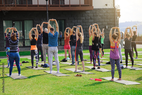 Sticker Group of adults attending a yoga class outside in yard