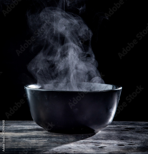 Steam of hot soup in a soup bowl with smoke on black background Poster